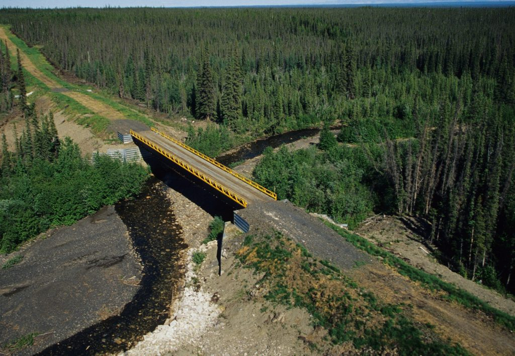 A bridge crosses a river in the boreal forest