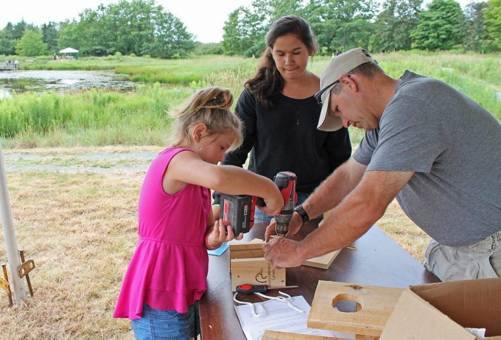 A volunteer helps a young girl build a nest box at a DUC event in Nova Scotia.