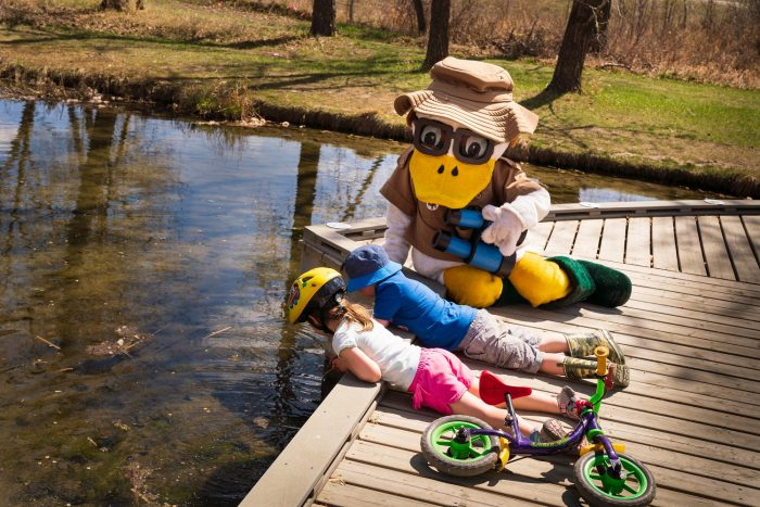 DU Duck and some of the event's youngest participants take a closer look into the marsh water.