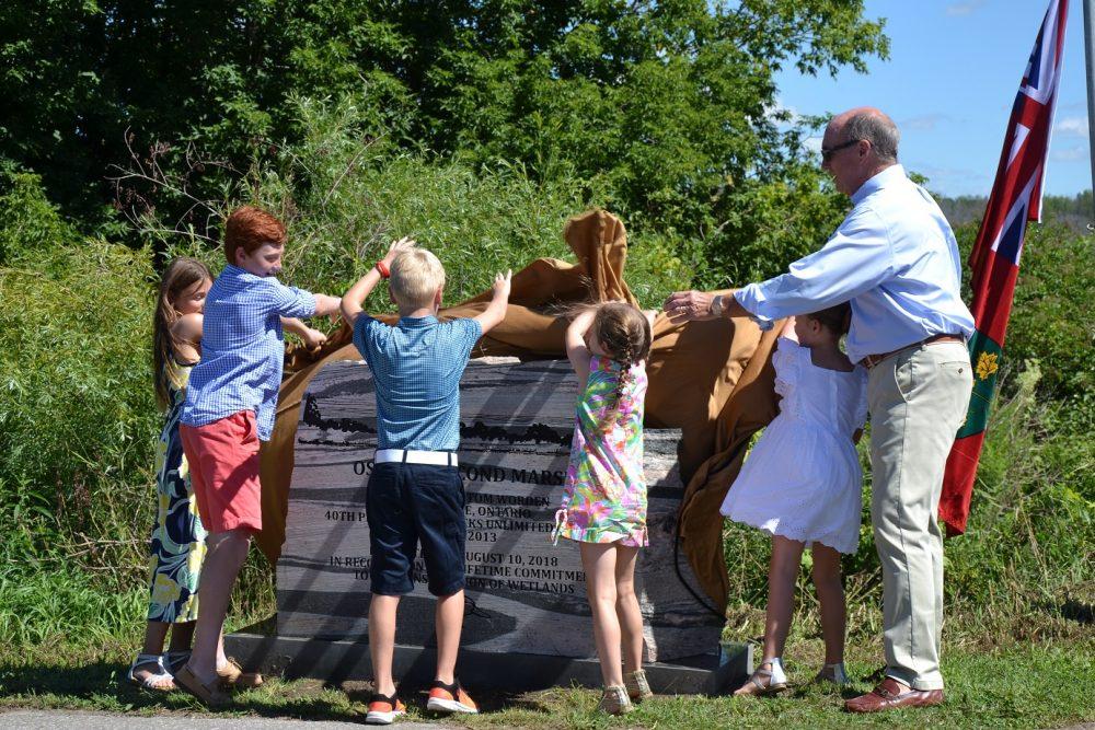 Tom Worden unveils the cairn at Oshawa Second Marsh, with help from grandchildren Hayden, Jack, Lauren, Paige and Kate.