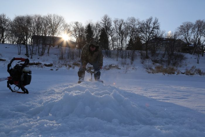 Pat Kehoe drills holes into the ice for a morning of fishing. Despite minus 34 C temperatures, Kehoe completes the task without gloves or a hat.