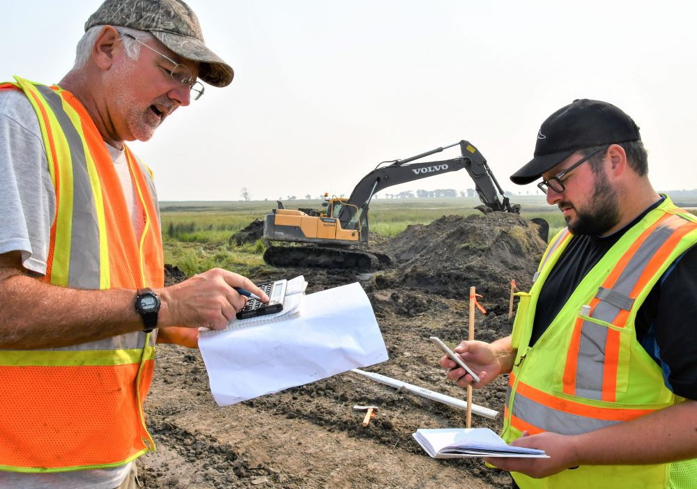 DUC engineer Dave Dobson (left) and fellow engineer, Patrick Lederman, check elevations at the work site about 40 kilometres northwest of Brandon.