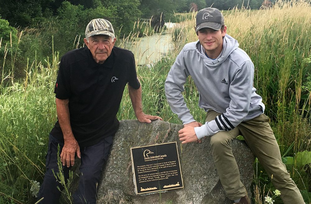 Dr. George Merry and his grandson, Angus, pose with the plaque at LaSalle Marsh honouring his family's gift of land to DUC.