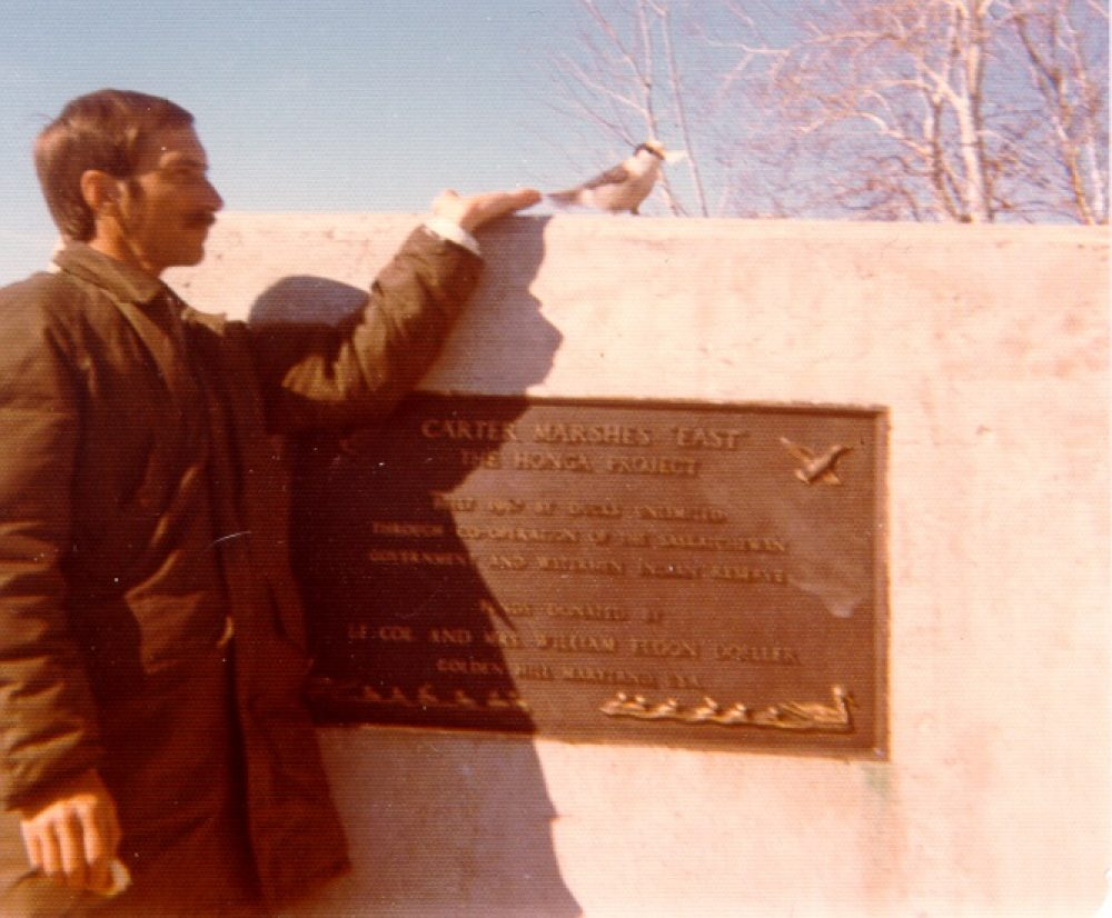 Dale Brydges poses with a feathered friend at a cairn and plaque at the Carter Marshes in Saskatchewan, 1976.