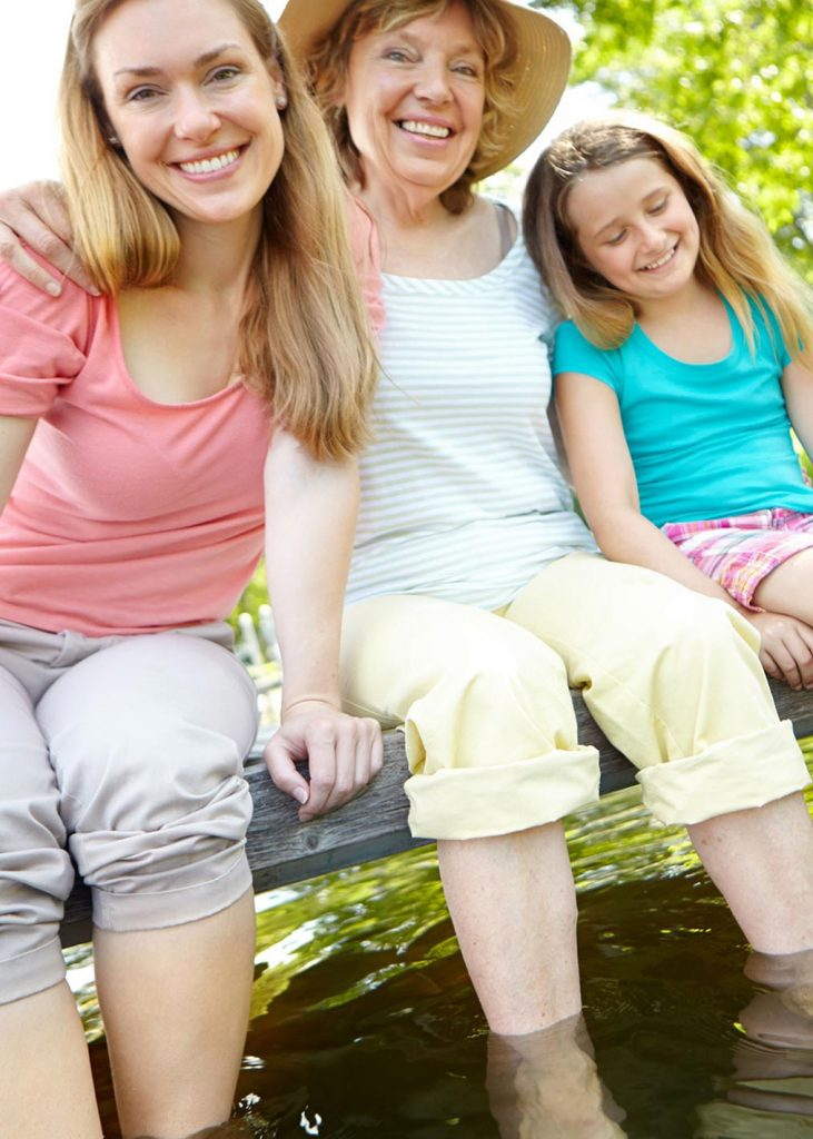 Photo of 3 generations of women sitting on a dock