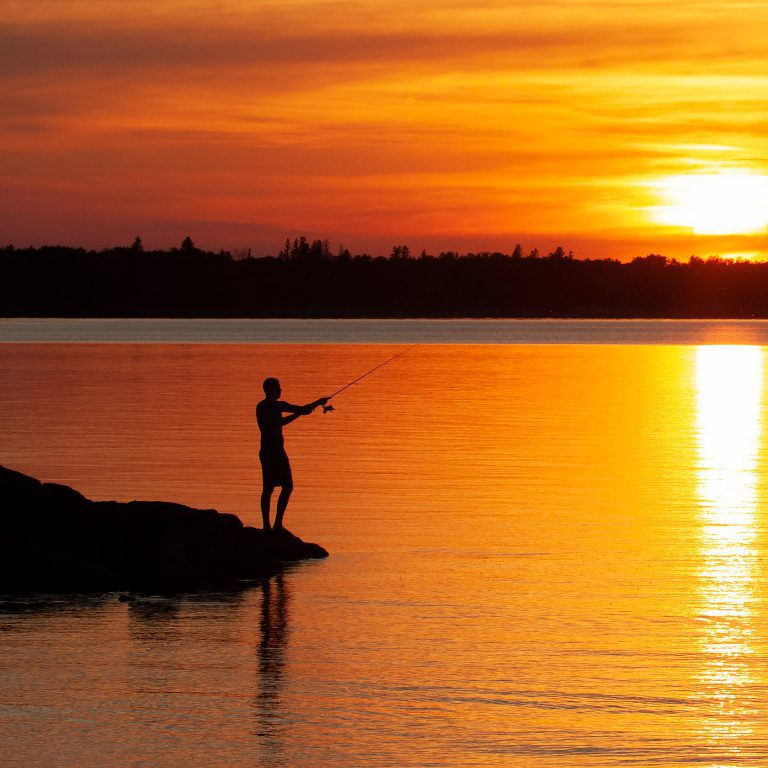 Man fishing off a dock at sunset