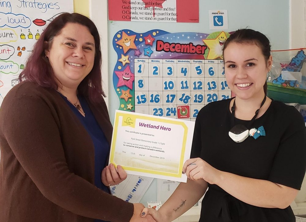 Ducks Unlimited Canada Education Specialist for NB and PEI Samantha Brewster shakes hands with Park Street Elementary School student-teacher Molly McIntyre while presenting her a Wetland Hero certificate on December 13, 2019 in Fredericton, N.B. McIntyre is currently enrolled in St. Thomas University, finishing a post-bac in education.