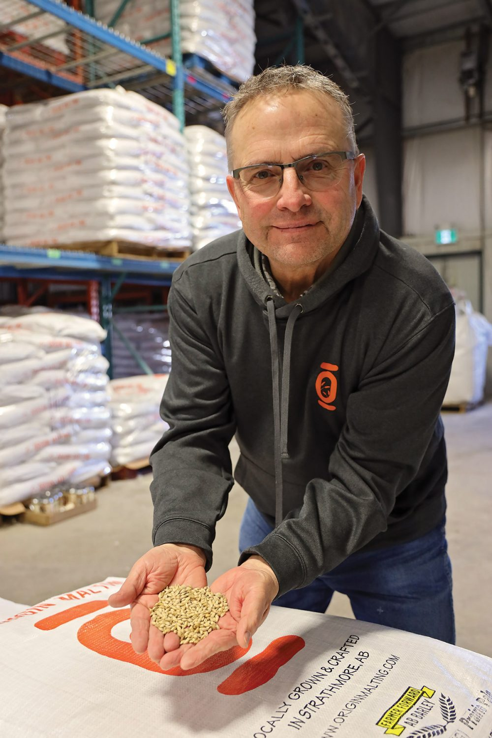 Spencer Hilton with a handful of barley to be used in his family's beer products. The Hiltons employ soil and wetland conservation systems on their farm to enhance the local environment.