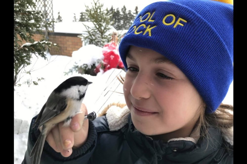 DUC Wetland Hero Lucy Harrison poses with a chickadee at Hilliardton Marsh, Ontario. Harrison learned her bird-handling skills as a volunteer and demonstrates the techniques to younger children.
