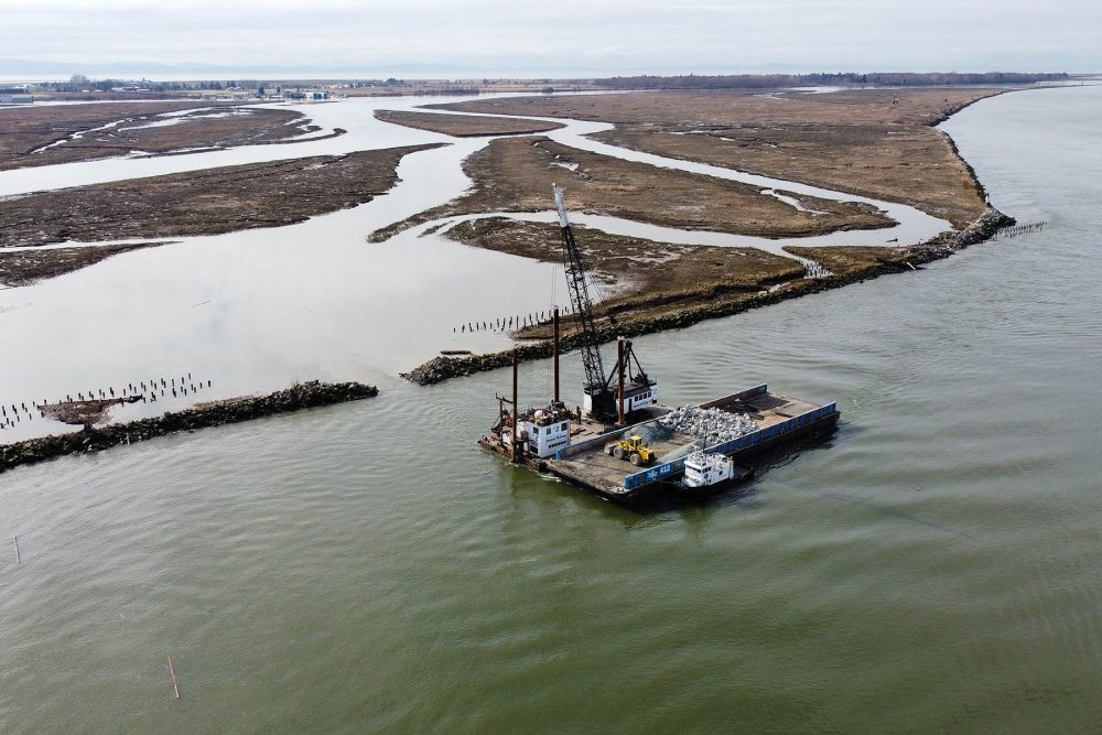 An aerial view of the Vancouver Pile Driving barge used to create three breaches in the Woodward Training Wall and Dam on the South Arm Marshes, located on the Fraser River.